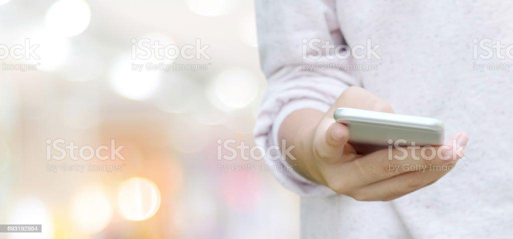 Mão usando telefone inteligente sobre o Borrão bokeh de fundo claro, conceito de negócios e tecnologia, marketing digital, seo, ecommerce, rede, internet das coisas - foto de acervo
