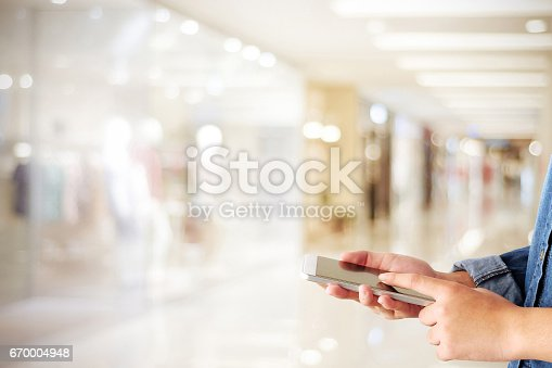 istock Hand using smart phone over blur store with bokeh light background, business and technology concept 670004948