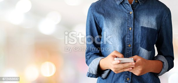 693192954 istock photo Hand using smart phone over blur store with bokeh light background, banner, business and technology concept, digital marketing, seo, e-commerce, lifestyles 672453532