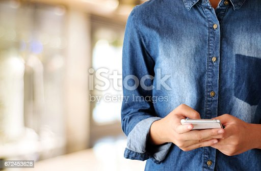 istock Hand using smart phone over blur store with bokeh light background, banner, business and technology concept, digital marketing, seo, e-commerce, lifestyles 672453628