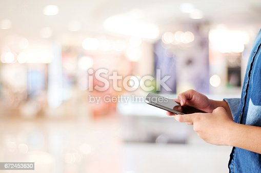 istock Hand using smart phone over blur store with bokeh light background, banner, business and technology concept, digital marketing, seo, e-commerce, lifestyles 672453630