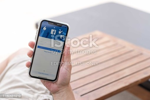 588359078 istock photo Hand  using smartphone IPhone XR with facebook application social media on screen, smart phone life style, mobile phone era in everyday lifestyle. 1150431010
