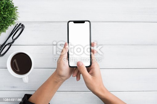 1084491176 istock photo Hand using smartphone on white wooden background 1084491186