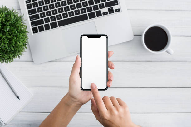 Hand using smartphone on white wooden background Female blogger searching information on internet websites, using smartphone with blank screen, top view female likeness stock pictures, royalty-free photos & images