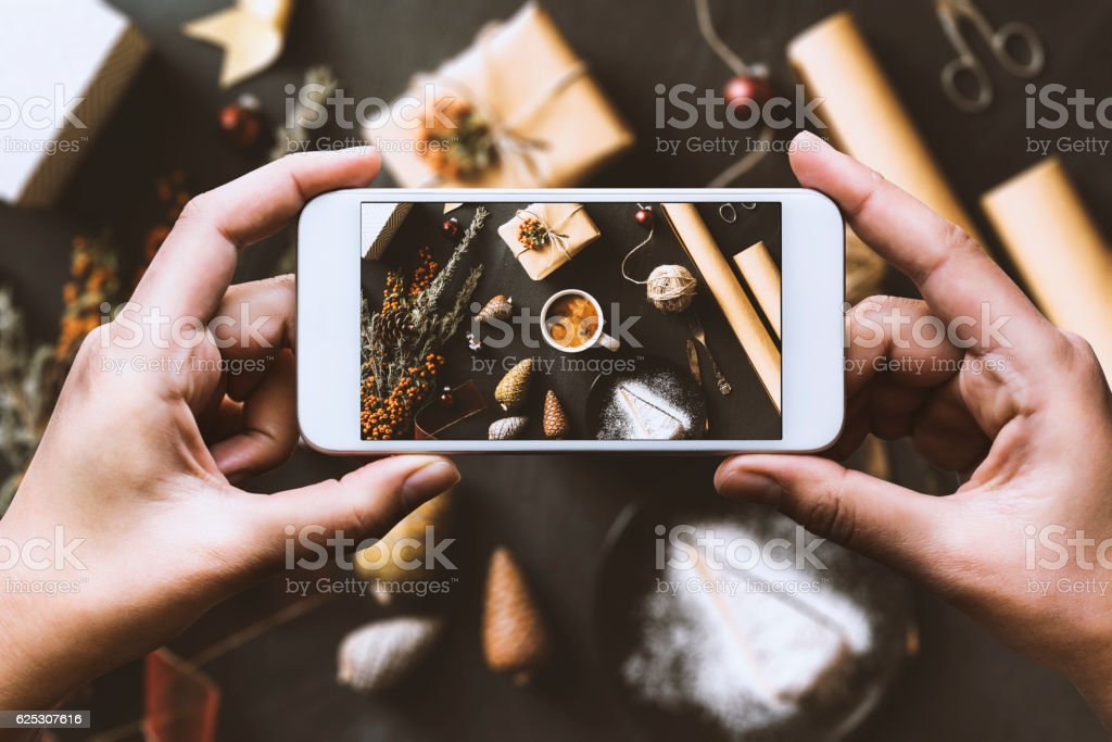 Hand using smartphone, sharing Christmas preparation on social media stock photo