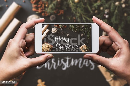 istock Hand using smartphone, sharing Christmas preparation on social media 628101144