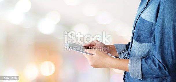 istock Hand using tablet over blur store with bokeh light background, banner, business and technology concept, digital marketing, seo, e-commerce 699767140