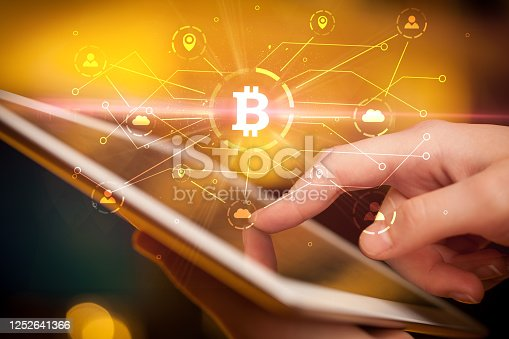 Hand using tablet with cryptocurrency bitcoin link network and online concept