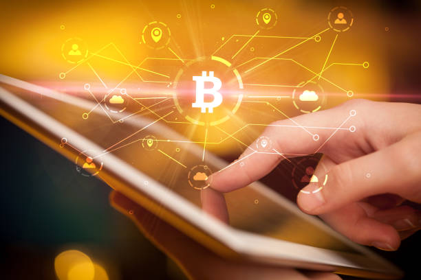 Hand using tablet with bitcoin link network and online concept stock photo