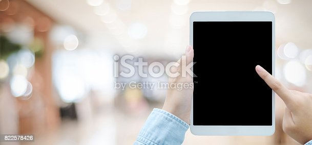 istock Hand using tablet with blank screen for mock up over blur store backgroun 822578426