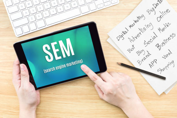 Hand using tablet with SEM (Search engine marketing ) word on screen with list of digital marketing features on paper on work table,Online business concept stock photo