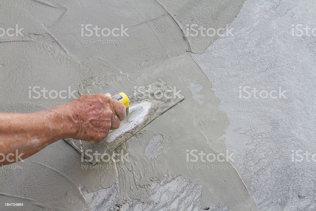 Hand using trowel on fresh concrete in construction site stock photo