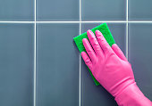 Hand in rubber gloves washes a tile.
