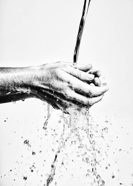 Hand washing in black and white under running water stock photo
