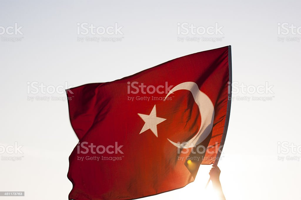 Hand waving the Turkish flag with sun on background stock photo