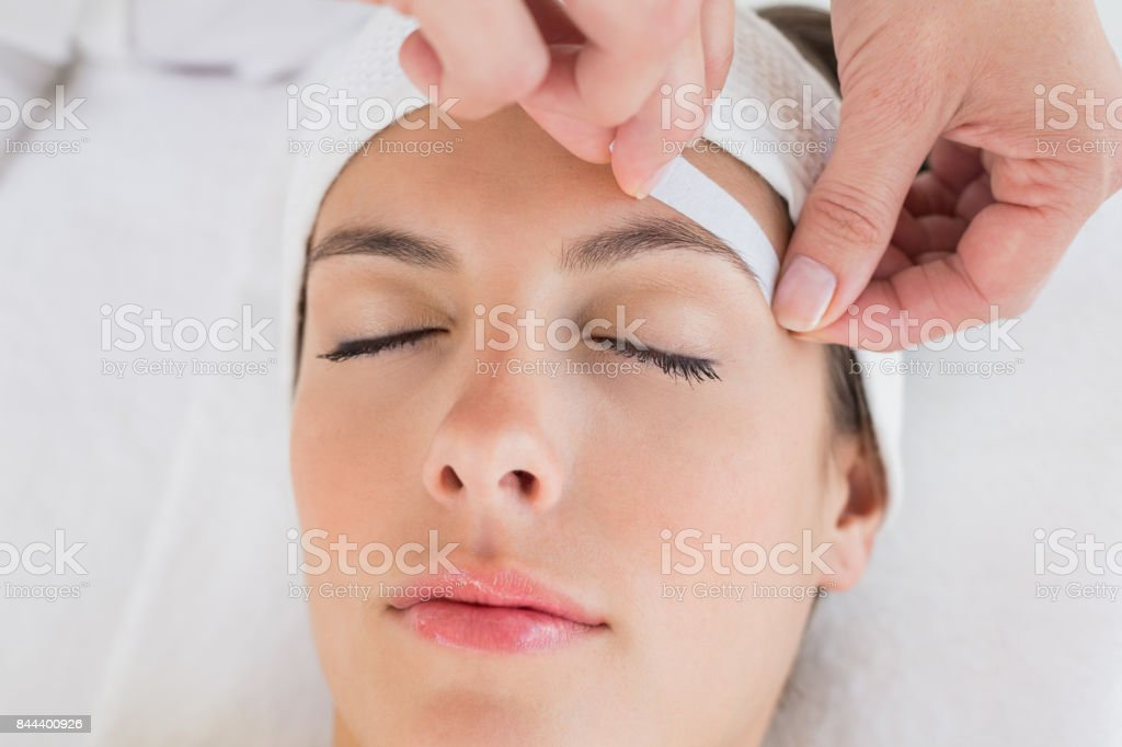Hand waxing beautiful womans eyebrow stock photo