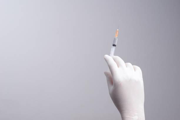 hand wearing latex glove holding syringe with a medicine - flu shot zdjęcia i obrazy z banku zdjęć
