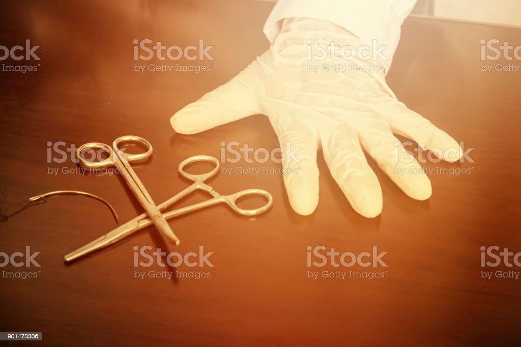 Hand wearing latex gloves examines medical forceps stock photo
