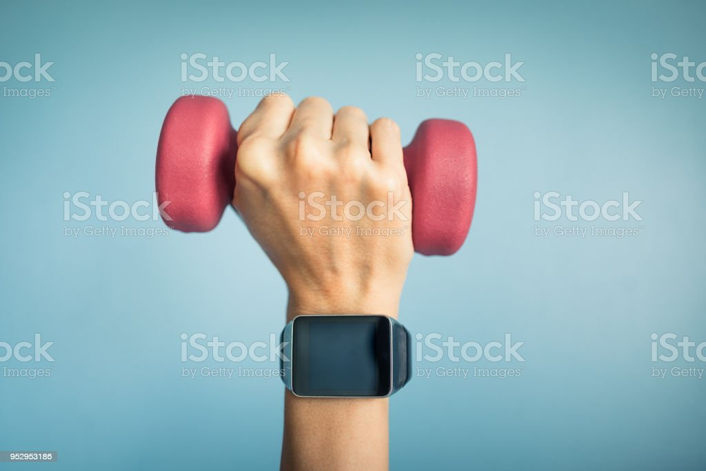 Hand wearing smartwatch and holding weight. stock photo