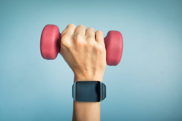 Hand wearing smartwatch and holding weight. Technology, fitness tracking concept fitness tracker stock pictures, royalty-free photos & images