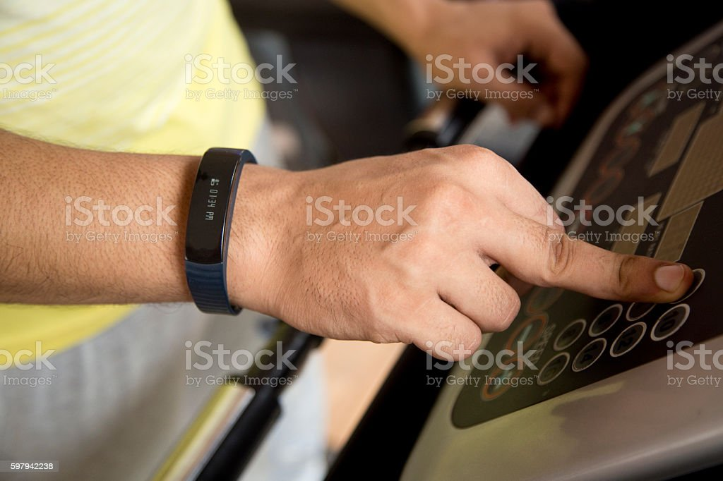 Hand wearing tracker and adjusting treadmill settings foto royalty-free