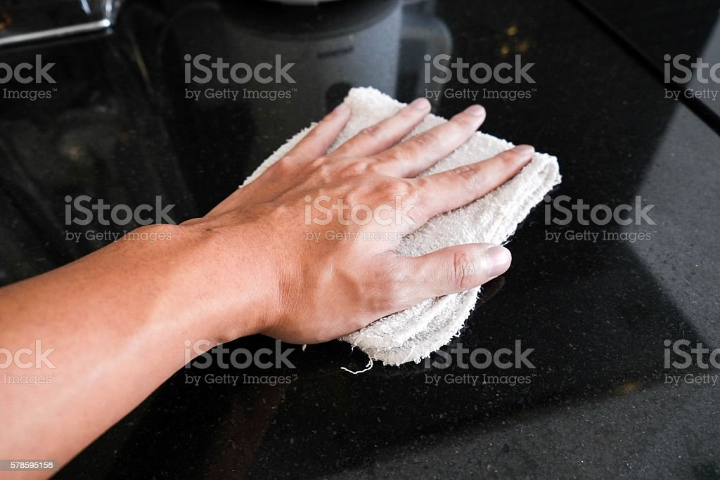 Hand wiping black marble stone counter bar stock photo