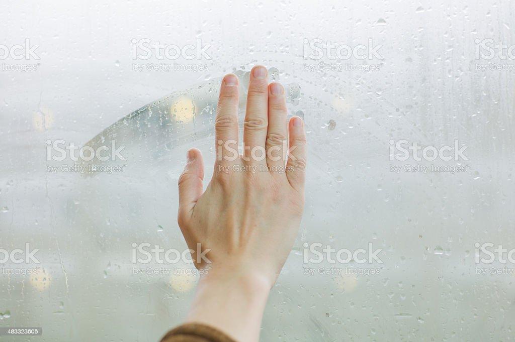 Hand wiping dew off window stock photo