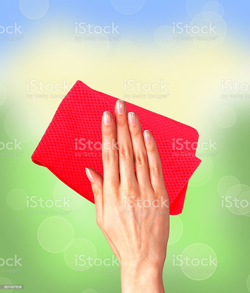 Hand wiping surface with red rag over bright window stock photo