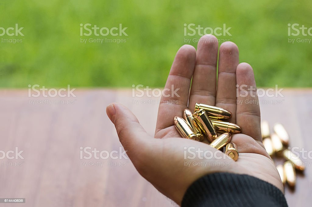 Hand with 9mm bullets. Hand holding bullets. stock photo