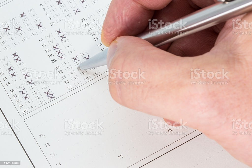 Hand with a ballpen taking an exam stock photo
