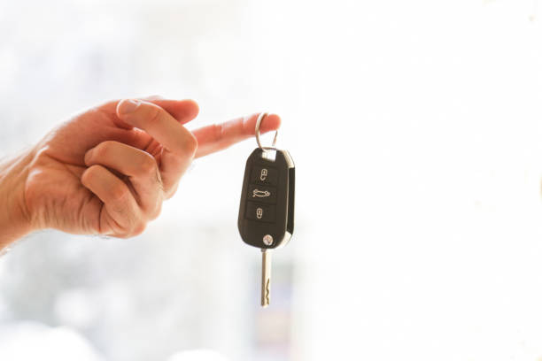 Hand with a car key. Isolated on white background stock photo