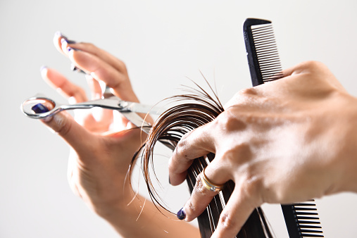 Hand with a comb cutting hair of woman
