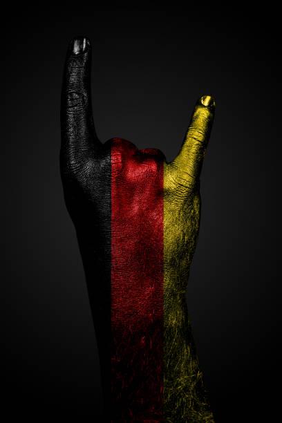 eine hand mit gezeichneter deutschland-fahne zeigt auf dunklem hintergrund ein ziegenschild, ein symbol für mainstream, metal und rockmusik. - teufel berlin stock-fotos und bilder