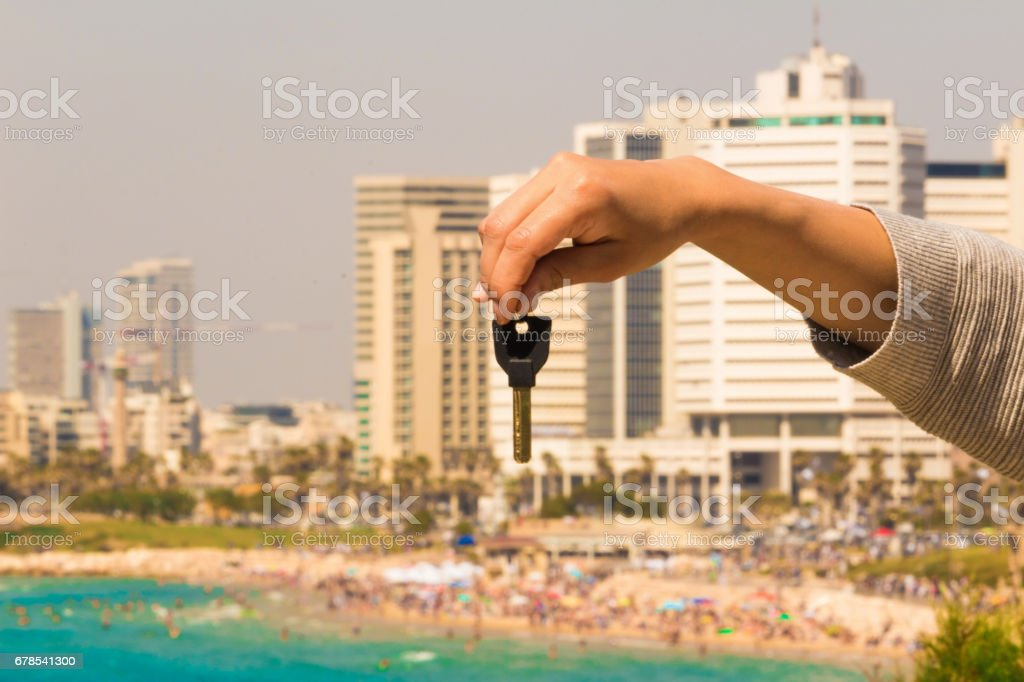 Hand with a key in the background of the sea with buildings and apartments stock photo