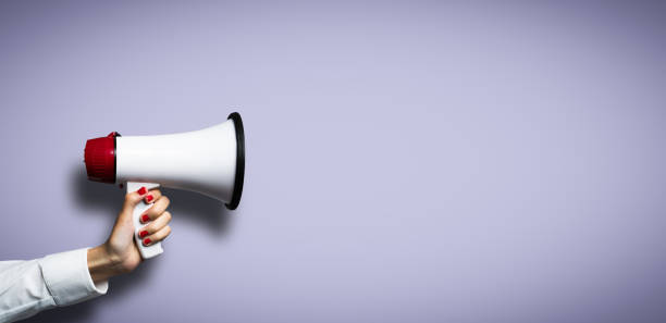 hand with a megaphone in front of an empty background stock photo