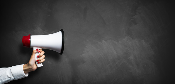 istock hand with a megaphone in front of an empty blackboard 1078587340