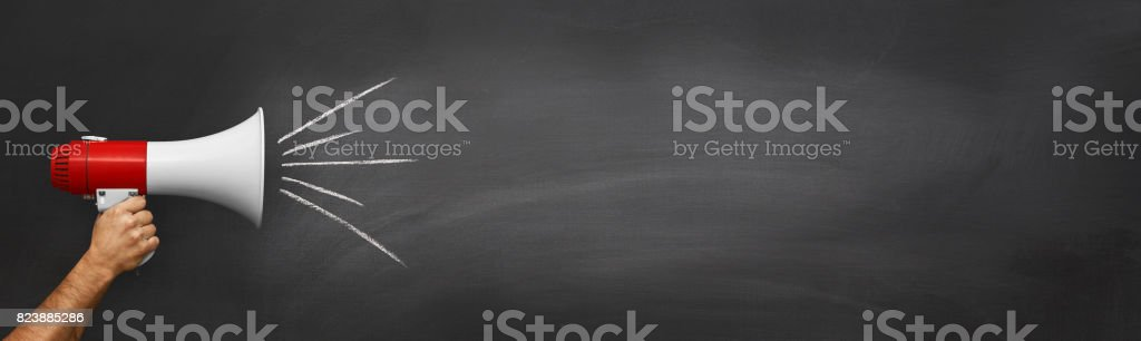 Hand with a megaphone in front of an empty blackboard stock photo