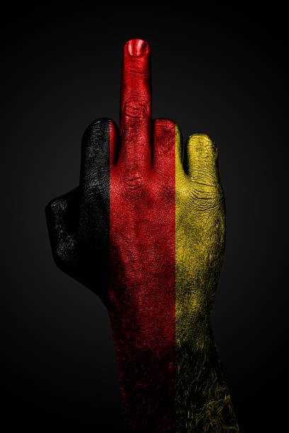 eine hand mit einer gemalten fahne deutschlands zeigt vor dunklem hintergrund den mittelfinger, ein zeichen der aggression. - teufel berlin stock-fotos und bilder