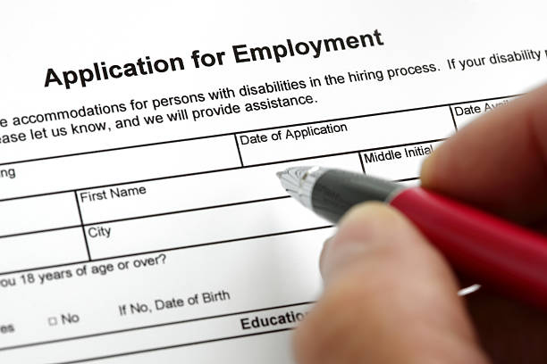 A hand with a pen filling out an application for employment Completing a job application form with focus on heading application form stock pictures, royalty-free photos & images