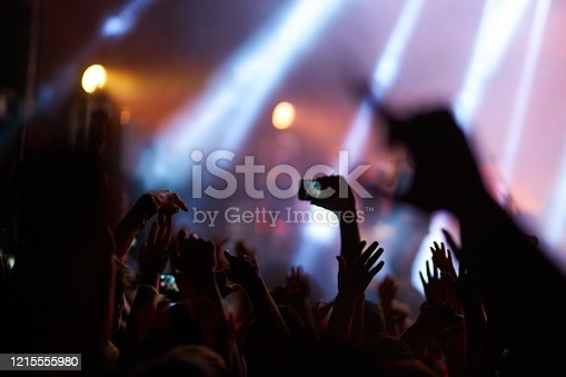 833314292 istock photo Hand with a phone records live music festival. 1215555980