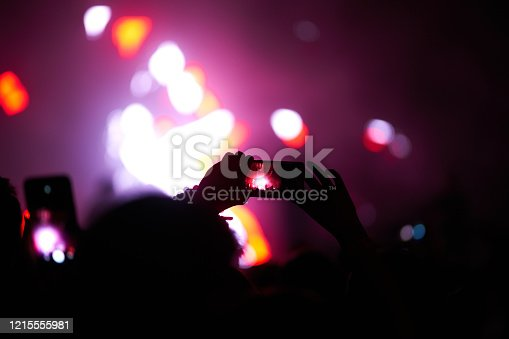 833314292 istock photo Hand with a phone records live music festival. 1215555981