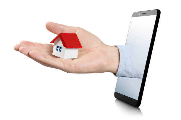 hand with a small house - hand holding phone стоковые фото и изображения