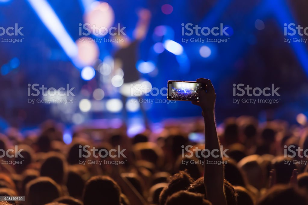 Hand with a smartphone records live music festiva stock photo