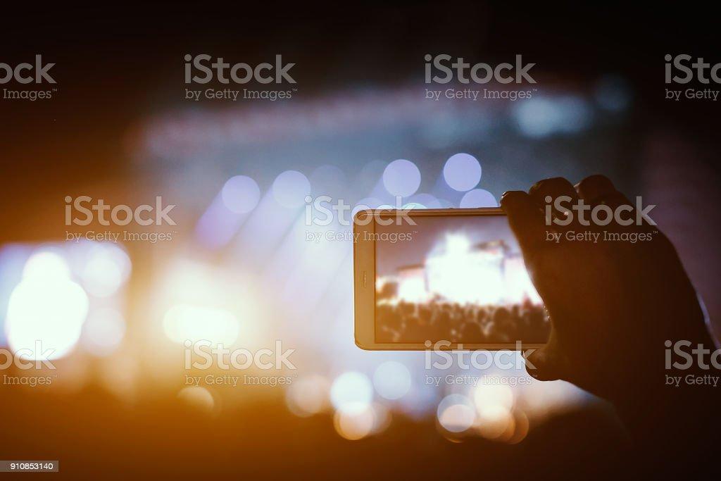 Hand mit einem Smartphone zeichnet live-Musik-Festival und nehmen Foto der Konzertbühne. – Foto