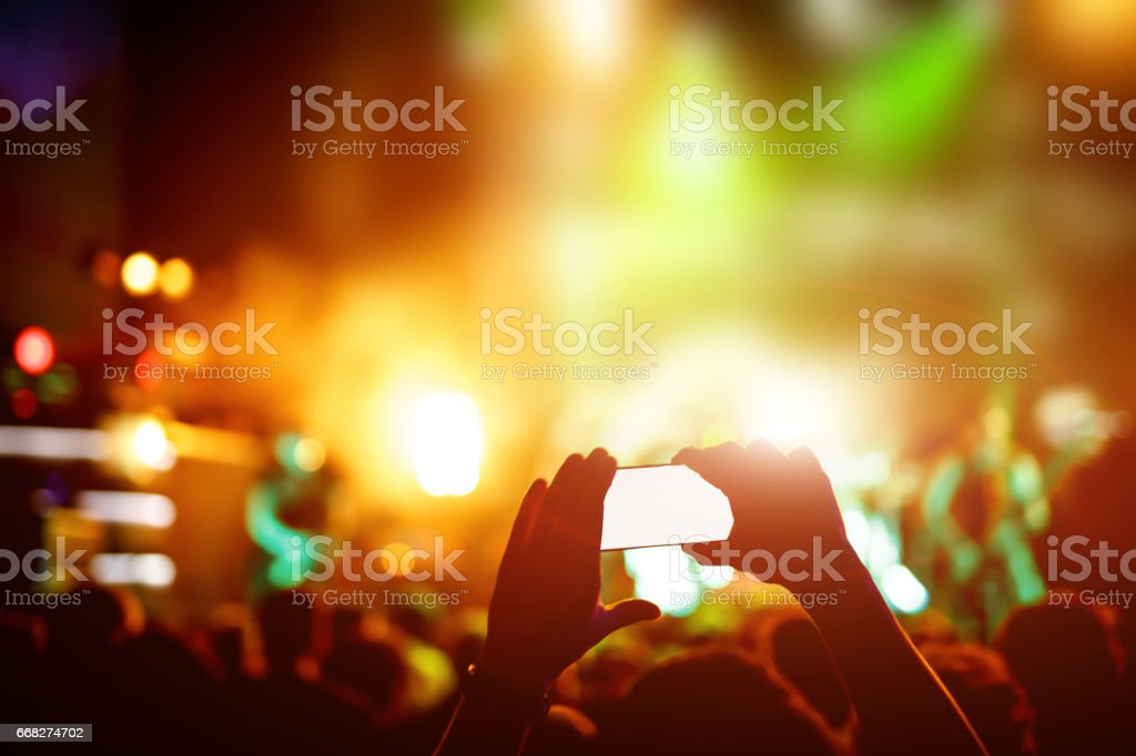 Hand with a smartphone records live music festival, live concert, show on stage foto stock royalty-free