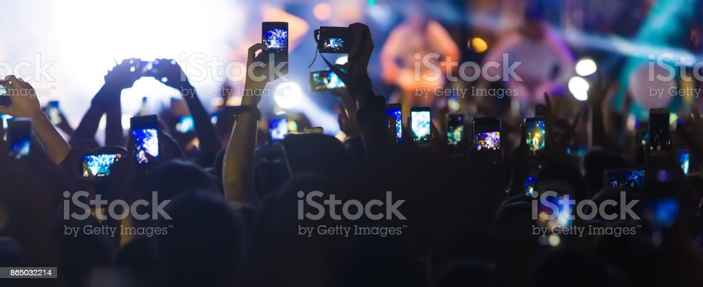 Hand with a smartphone records live music festival stock photo
