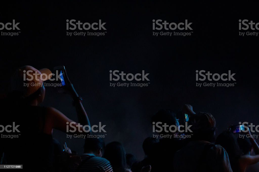 Hand with a smartphone records live music festival, Taking photo of...