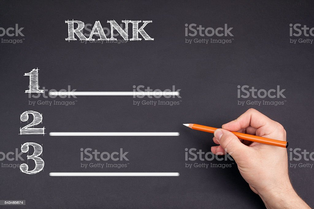 Hand with a white pencil writing: Rank blank list – Foto