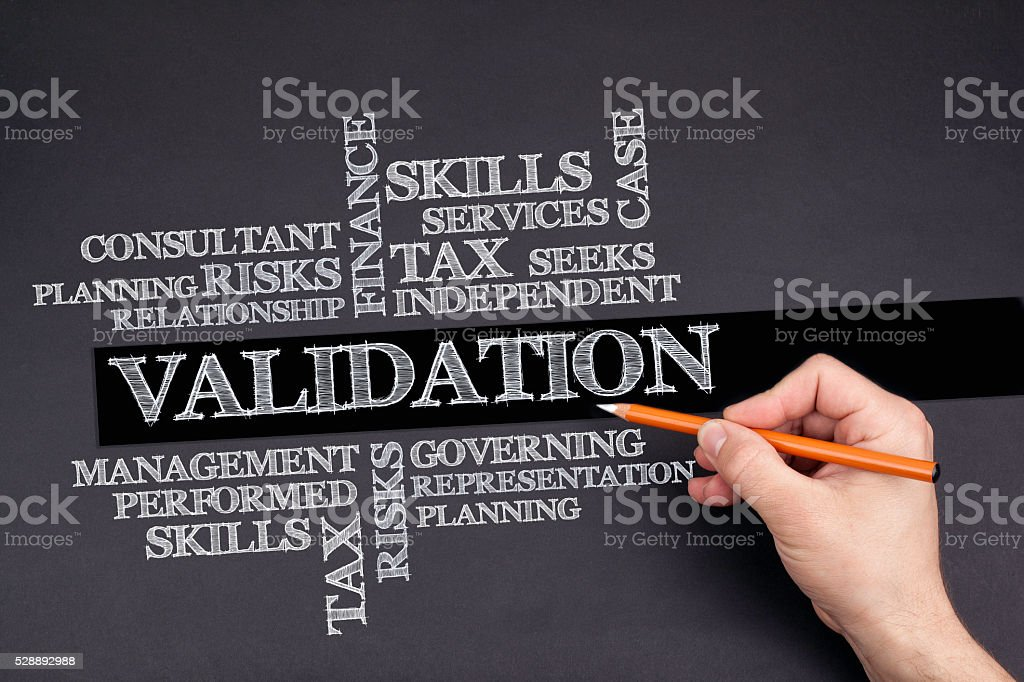 Hand with a white pencil writing: VALIDATION word cloud stock photo
