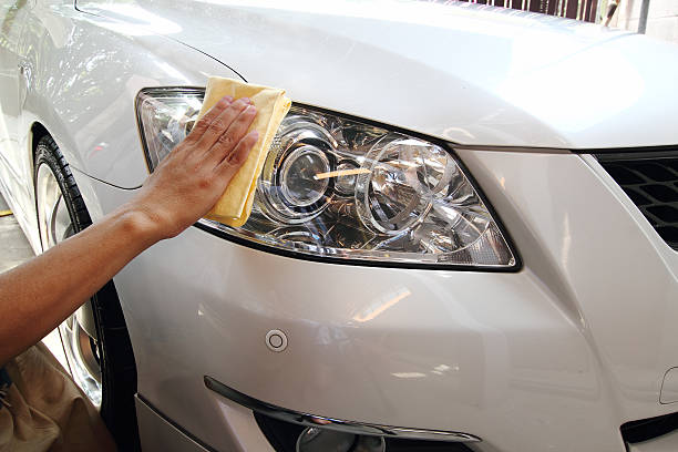 Hand with a wipe the car polishing Hand a wipe microfiber the white car polishing headlight stock pictures, royalty-free photos & images